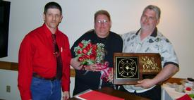 Chief Tim Jerome, Gloria Enslow, and Firefighter of the Year William Enslow