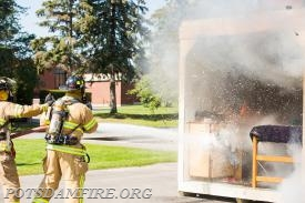 Firefighters J. Bradish and D. Monahan extinguish the mock dorm room  *Photo Courtesy of SUNY Potsdam