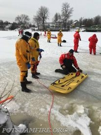 Dive Master D. Taylor explaining the different components of the rescue sled to J. Kozak and M. Seymour.