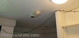 Fire Safety Violation: String lights hanging from the ceiling along with a bag covering the smoke detector