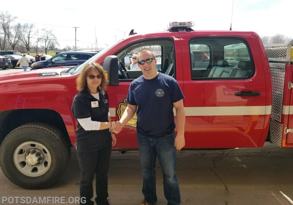 (FF M. Maroney) accepting the donation from a Save-A-Lot employee.